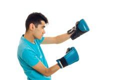 Młody facet w koszulki błękitnych stojakach z ukosa w bokserskich rękawiczkach odizolowywa na białym tle Obraz Stock