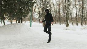 M?ody facet w masce na jego twarzy w czerni, bawi si? kostium, wykonuje ?wiczenia, skokowa arkana w ?nie?ystym parku zdjęcie wideo