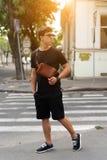 Młody facet w round okularach przeciwsłonecznych pozuje na kamerze zdjęcie stock