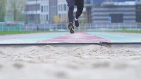 Młody facet w sportswear przyśpiesza i skoki w piasku przed kamera piaskiem rozpraszają spod cieków a zbiory wideo