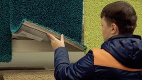 Młody facet wybiera dywan w materiału budowlanego sklepie, w celu kupienia zdjęcie wideo
