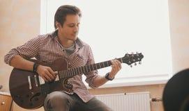 Młody faceta muzyk komponuje muzykę na gitarze i sztuki w kuchni, zakończenie up obrazy stock