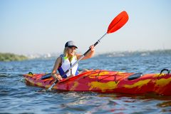 Młody Fachowej kobiety Kayaker Paddling kajaka na rzece pod Jaskrawym ranku słońcem Sporta i aktywnego stylu życia pojęcie Obraz Stock
