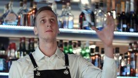 Młody fachowy barman w akci z potrząsaczem i butelką robi koktajli/lów napojom Zdjęcia Royalty Free