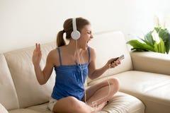 Młody fan muzyki jest ubranym hełmofony śpiewa słuchający mp3 na smar Fotografia Stock