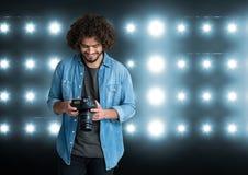 młody fotograf patrzeje fotografie na kamerze stadiów światła behind zdjęcie stock