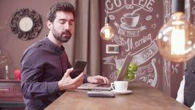 Młody freelancer używa jego smartphone robić zapłacie przy prętowym kontuarem zbiory