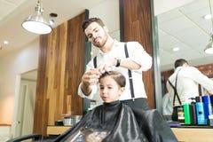 Młody fryzjera męskiego tytułowania chłopiec ` s włosy Po ostrzyżenia W sklepie fotografia stock