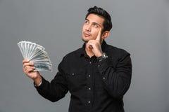 Młody główkowanie koncentrujący mężczyzna mienia pieniądze fotografia royalty free