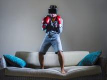 Młody gamer mężczyzna używa VR gogle kłobuk i bokserskie rękawiczki bawić się symulanta 3D walczymy wideo grę ma zabawę na domowe zdjęcia stock