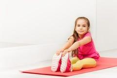 Młody gimnastyczki obsiadanie na maty i rozciągania nogach obrazy stock
