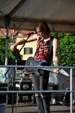 Młody gitarzysta, członek muzyki rockowej grupa Paranoiczny, stojak w scenie przed mikrofonem zdjęcie stock