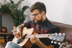 Młody gitarzysty modniś trzyma gitary obsiadanie wyszukuje smartphone sprawdza środki w domu fotografia stock