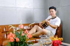 Młody gitarzysty modniś z gitarą na brown kanapie w domu obrazy stock