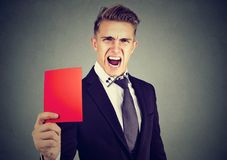 Młody gniewny mężczyzna arbiter pokazuje czerwoną kartkę zdjęcia stock