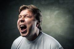 Młody gniewny mężczyzna nad zmroku popielatym tłem Zdjęcie Royalty Free