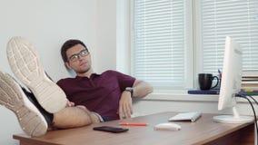 Młody gnuśny urzędnik relaksuje w biurze z jego w szkłach iść na piechotę na stole w nowożytnych biurowych miotanie kawałkach zdjęcie wideo