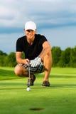 Młody golfowy gracz na kursowym kładzeniu Zdjęcia Royalty Free