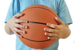 Młody gracz koszykówki chłopiec trzyma koszykówkę w jego rękach zdjęcie royalty free