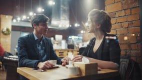 Młody heteroseksualny pary datowanie opowiada kawę w wygodnym nowożytnym café i pije, zbiory