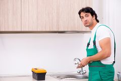 Młody hydraulika naprawiania klepnięcie przy kuchnią obraz royalty free