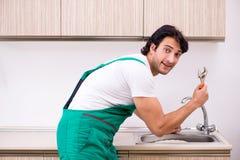 Młody hydraulika naprawiania klepnięcie przy kuchnią zdjęcie stock