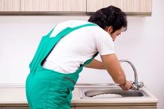 Młody hydraulika naprawiania klepnięcie przy kuchnią zdjęcia stock