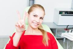 Młody i ładny żeński pacjent przy dentystą pokazuje zwycięstwa gestu zdjęcie stock