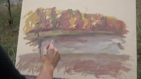 Młody i kreatywnie artysta maluje obrazek na kanwie w na wolnym powietrzu, mężczyzny farby muśnięcie na kanwie która, zdjęcie wideo