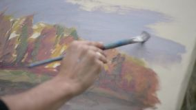 Młody i kreatywnie artysta maluje obrazek na kanwie w na wolnym powietrzu, mężczyzny farby muśnięcie na kanwie która, zbiory
