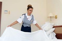 Młody i piękny gosposi dziewczyny podesłania łóżko zdjęcie stock
