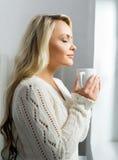 Młody i piękny kobiety pić kawowy okno i patrzeć je fotografia royalty free