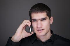 Młody i przystojny mężczyzna opowiada na telefon komórkowy Obrazy Stock