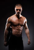 Młody i silny męski bodybuilder na czerni Obrazy Stock