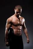 Młody i silny męski bodybuilder na czerni Zdjęcia Royalty Free