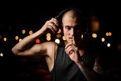 Młody i tatuujący klub nocny DJ w hełmofonach czuje muzykę obraz royalty free