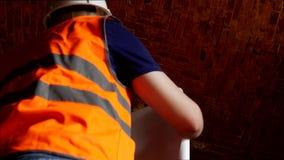 Młody inspektor egzamininuje gęstość cegła na suficie stary budynek i brickwork, zakończenie zdjęcie wideo