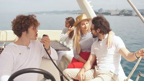 Młody kędzierzawy mężczyzna żegluje denną łódź, żegluje w firmie jego przyjaciele, faceci i dziewczyny siedzi beside radośni, cie zbiory