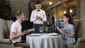 Młody kelner Bierze rozkaz od faceta i Brunet kobiety zbiory