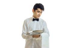 Młody kelner z czarni włosy obniżał jego kierowniczego puszek i trzymać tacę Zdjęcie Stock
