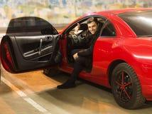 Młody kierowcy obsiadanie w sportowym samochodzie pokazuje aprobaty obraz stock