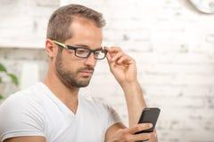Młody kierownictwo patrzeje jego telefon komórkowego Zdjęcia Royalty Free
