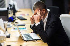 Młody kierownik przy miejscem pracy Młody człowiek pracuje na komputerze w biurze Zdjęcia Royalty Free