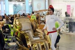 Młody kobieta model obok złotego krzesła dla piękna Intercharm XII Międzynarodowej mydlarni i kosmetyka Moskwa powystawowej jesie Fotografia Royalty Free