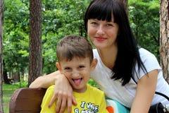 Młody kobieta modela obsiadanie na ławce w parku z jej małym synem w żółtej koszulce Syn zgina patrzeć kamerę zdjęcia royalty free