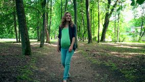 Młody kobieta w ciąży chodzi samotnie w parku i muska jej podbrzusze zdjęcie wideo