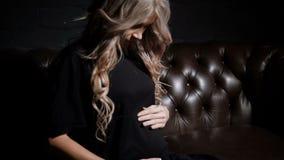 Młody kobieta w ciąży dotyka jej brzucha w czerni sukni siedzącym półzwrocie w ciemnym pokoju na dużej brown rzemiennej kanapie zbiory wideo