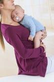 Młody kobieta w ciąży mienia dziecka dosypianie w ona ręki Zdjęcia Stock
