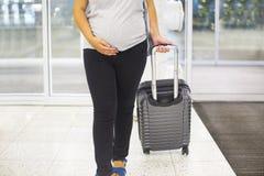 Młody kobieta w ciąży z walizką przy lotniskiem fotografia royalty free