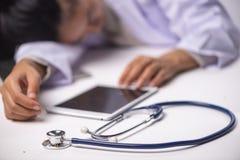 Młody kobiety lekarki dosypianie przy jej biurkiem pracuje nad laptopem i zdjęcia royalty free